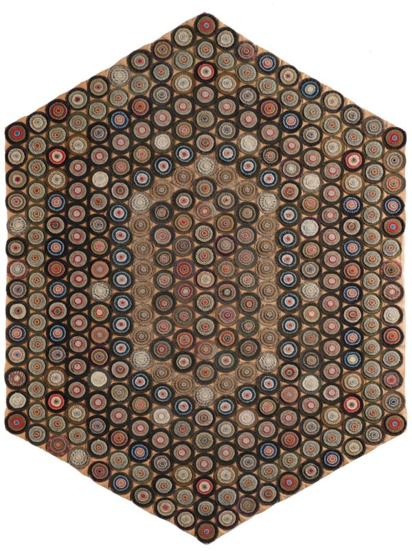 Multi-colored rug with felt penny cutouts on black all on tan/rose color background