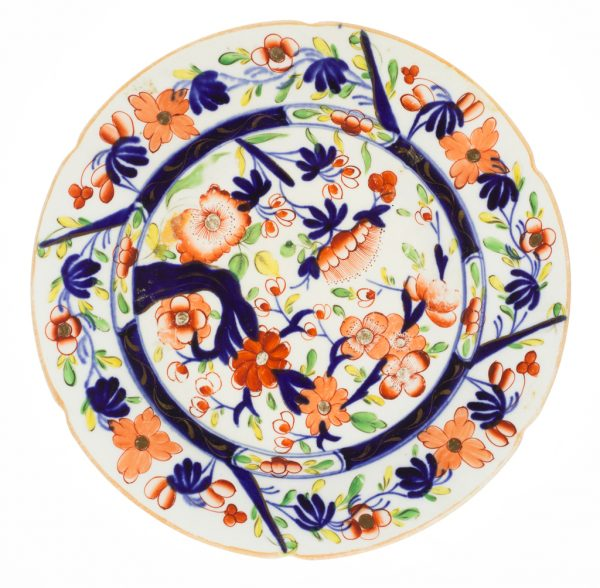 A plate in blue, orange and gold on cream.