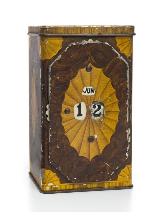 A tin box in green and yellow. One side has an adjustable calendar.