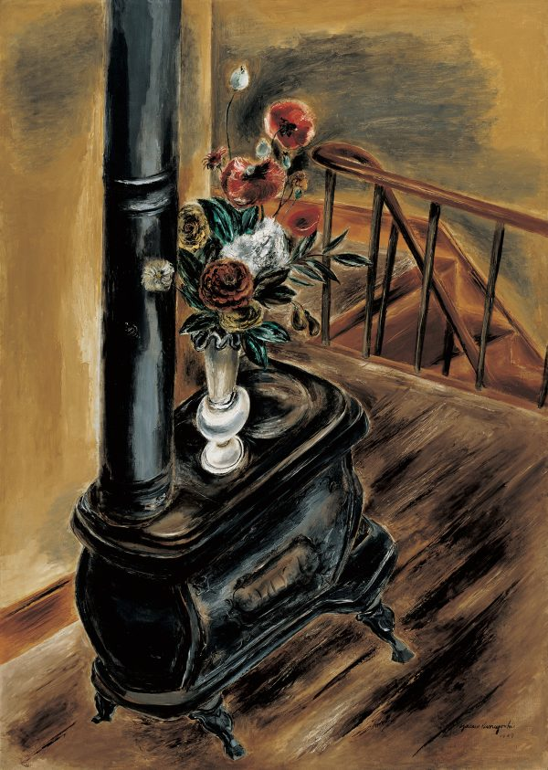 A wood burning stove with a vase of flower on top stands in a room with a stair case in the background.