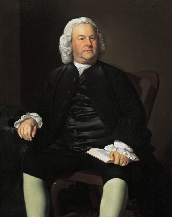 A portrait of a man in a white wig holding an open book. His suit is black with white leggings.
