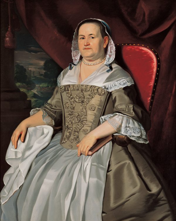 A woman seated on a red chair. She holds a closed book and wears a lace covering over her hair.