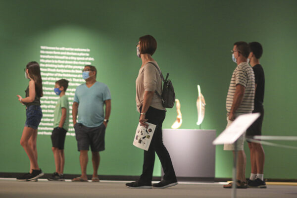 Interior view of the galleries with visitors walking through the Singletary exhibition wearing masks