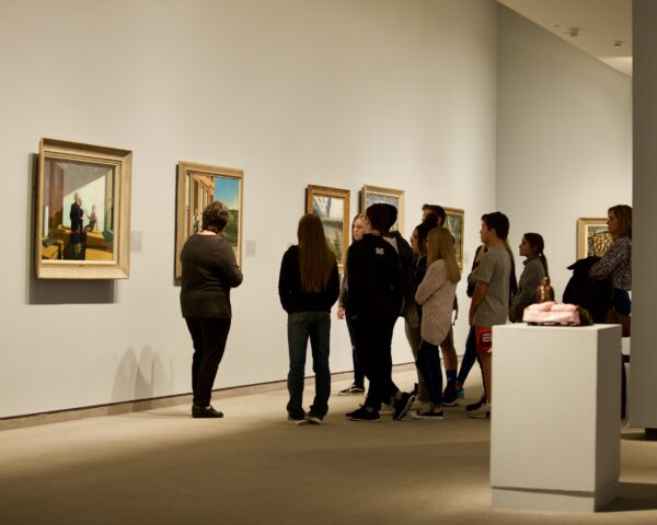 Interior view of the galleries with a docent leading a group of adults on a tour