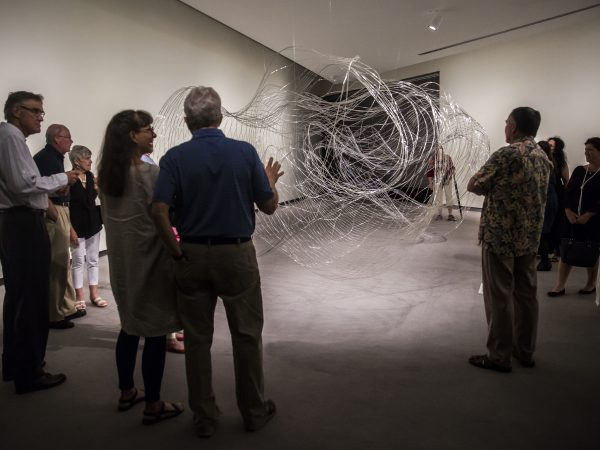 Interior image of adults in a gallery looking at a glass art installation