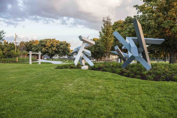 Photo of two large metal sculptures surrounded by green grass and green bushes