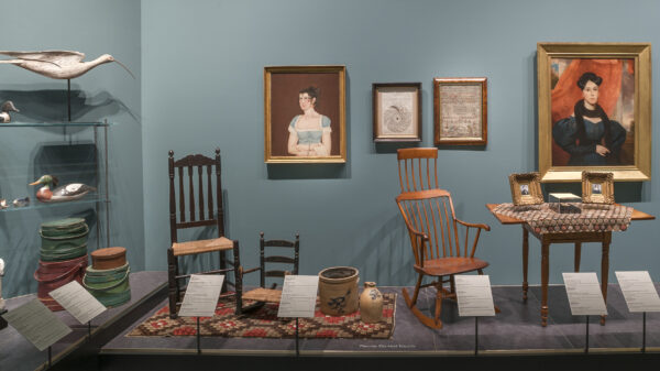 Photo of early American decorative arts includes two chairs, one rocking chair, two paintings of somen, a desk, framed photos, a rug, a milk jub, a crock and a duck decoy