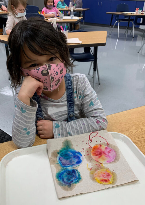 Photo of a little girl wearing a mask looking at the camera with her circular art pieces in front of her