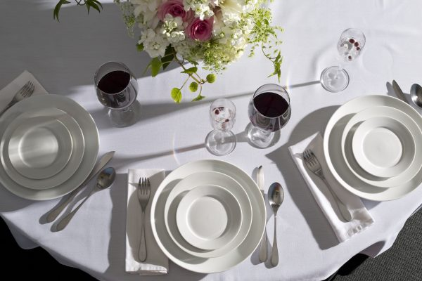 Overhead view of table with white tablecloth, plates, glasses, silverware and a floral centerpiece