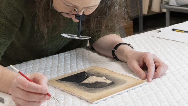 Woman examining a print on a table