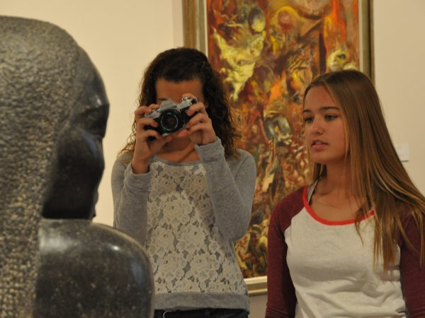 Interior view of two high schools girls photographing a sculpture