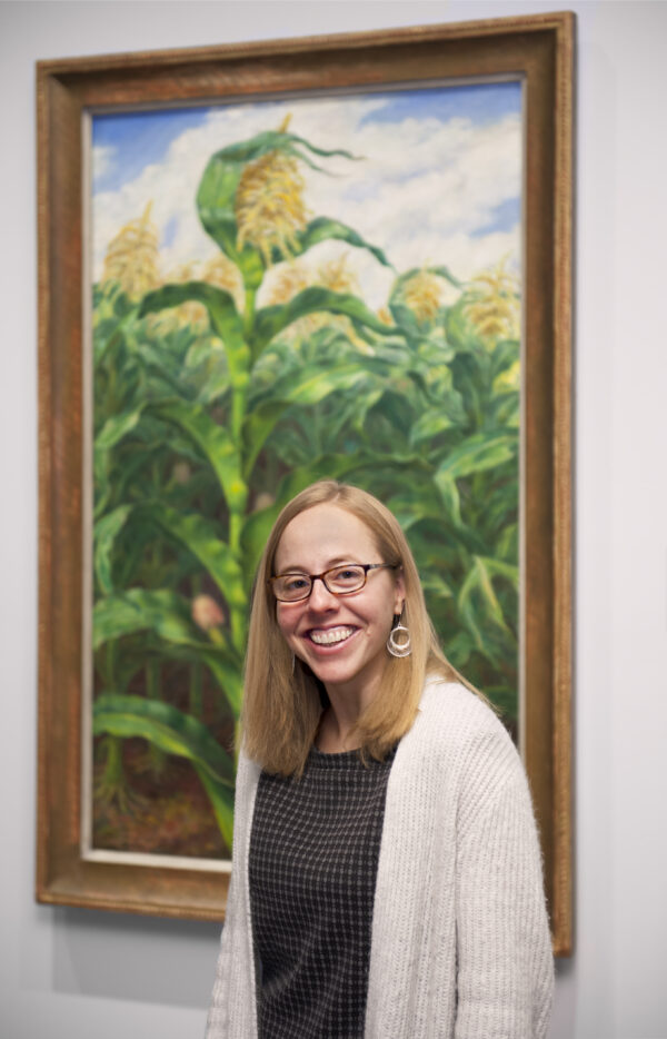 Woman wearing a grey sweater and blue dress in front of a painting of a cornfield with green stalks and yellow tassles