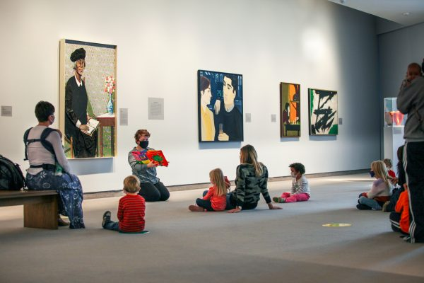 Adults and kids sitting on the floor of the galleries listening to a presentation