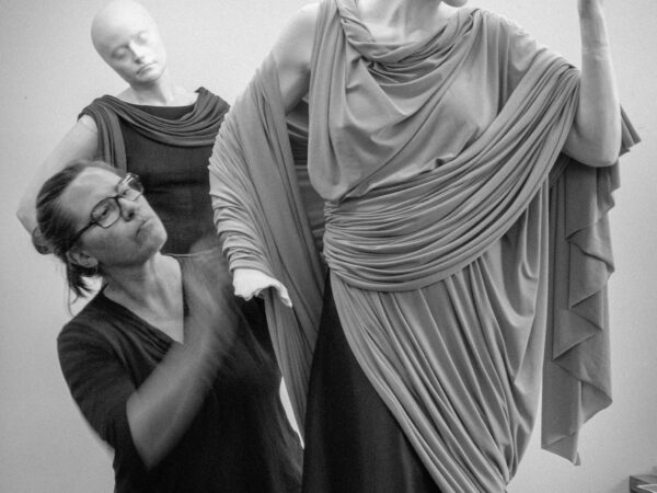 Photo of woman wearing glasses working with mannequins draped in fabric