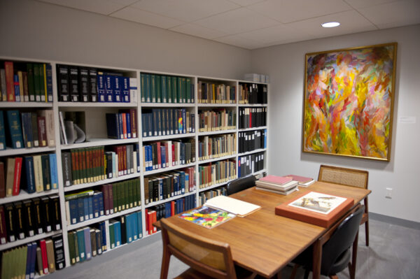 Interior view of the Library with a table, three chairs, books on the table, shelves filled with books in the background and a colorful abstract painting on the wall
