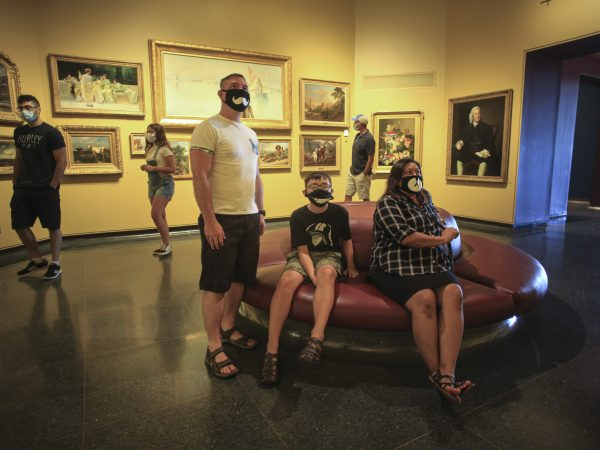Visitors in the Rotunda Gallery sitting on a round ottoman and looking at paintings on the wall