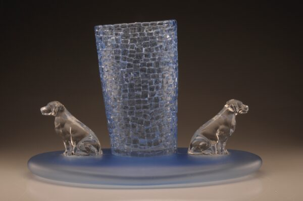 Light blue blown glass vase on an oversized circular base with clear crystal glass dogs on two sides