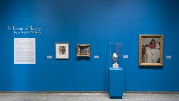 Interior view of galleries with paintings on the wall and a sculpture on a pedestal