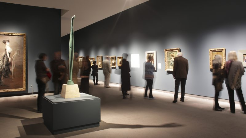 Interior view of galleries with adults looking at artwork on the wall from French Impressionist painters