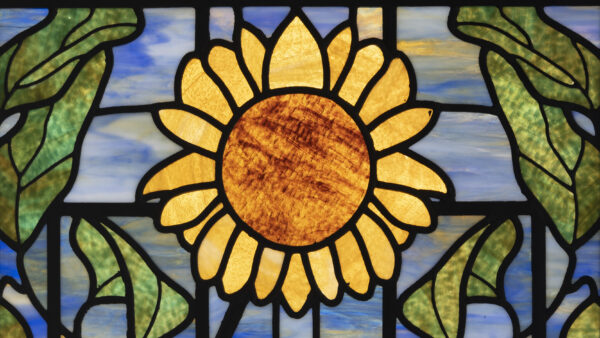 Stained glass window with a yellow sunflower in the center surrounded by green leaves with a blue sky in the background