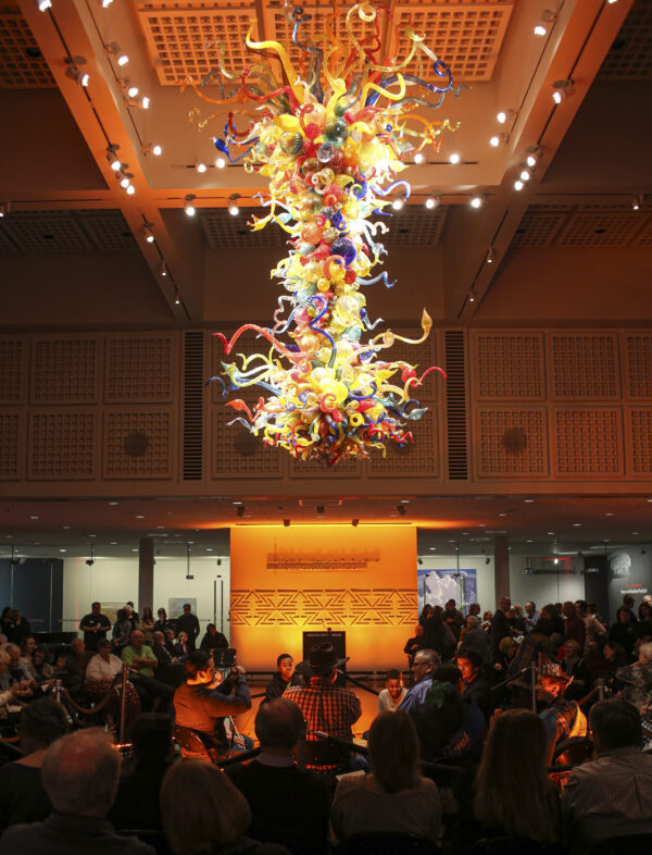 Photo of the Chihuly Chandelier at night with people sitting at tables and chairs underneath it