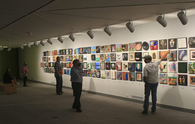 Interior image of adults in a gallery looking at colorful paintings on the wall