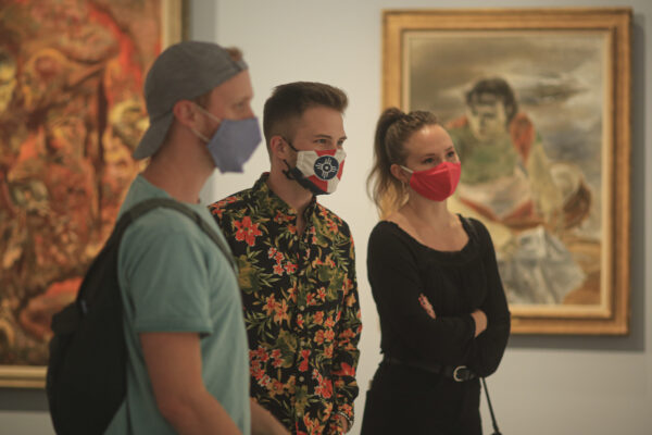 Interior view of visitors in the galleries wearing masks