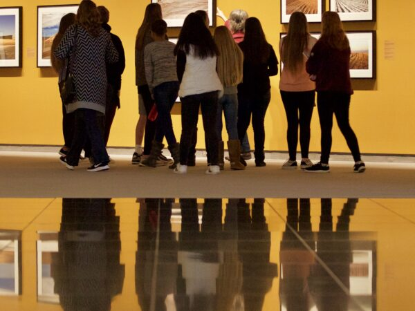 Photo of a half-dozen high school students with their backs to the camera looking at photography of Kansas on the wall