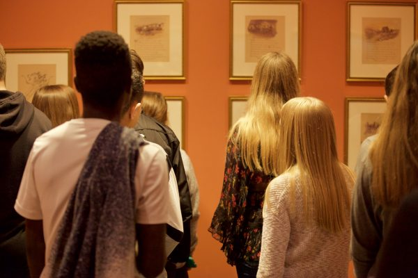 Interior view of a group of students looking at prints on the wall