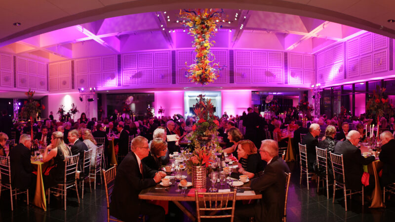 Photo of dozens of people sitting at decorated tables and chairs eating dinner in the Farha Great Hall with the large Chihuly Chandelier in the top center