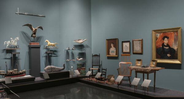 Interior image of galleries showing WAM's Americana collection of decorative arts with two portraits on the wall, two wooden chairs, a rug, two duck decoys, a wooden eagle