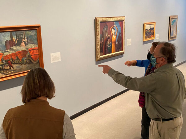 Three adults in the gallery, two pointing at a painting.
