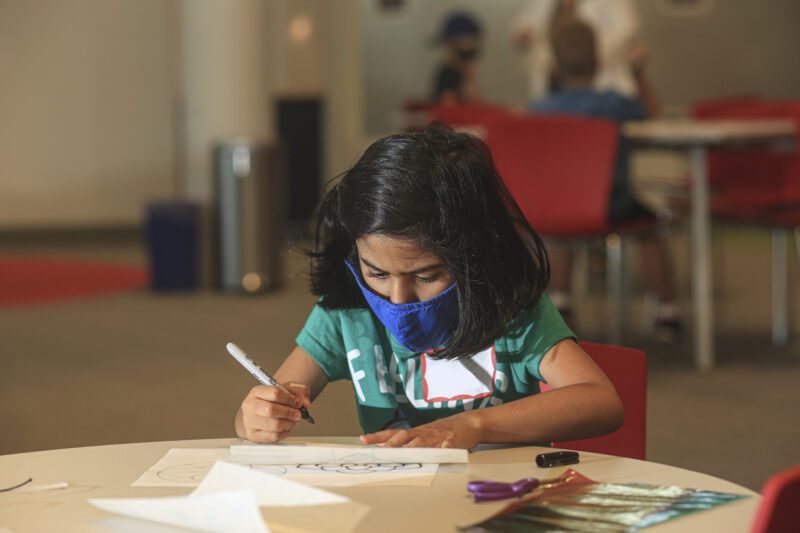 Young girl sitting at a table, wearing a mask, drawing on paper