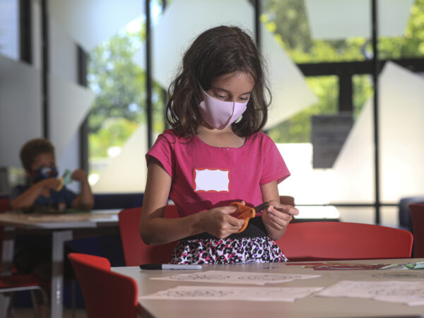 Young girl wearing a pink shirt and a mask sitting at a table holding scissors and cutting paper