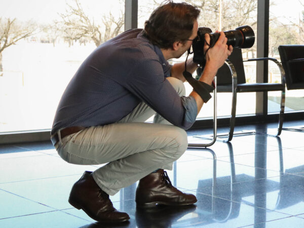 Man crouched down facing his camera off to the right side of the frame