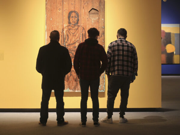 Silhouette of three men in front of painting in the gallery