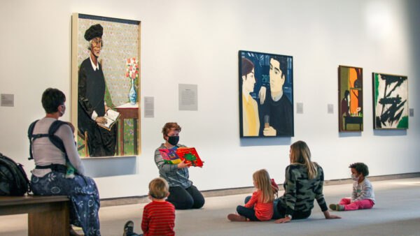 Young children and parents sitting on the floor in a gallery, with an adults sitting in front of a painting reading a picture book.