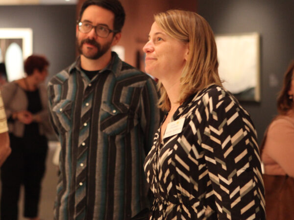 Two art educators, one woman and one man, standing sideways from the camera looking at art from the Georgia O'Keeffe exhibition