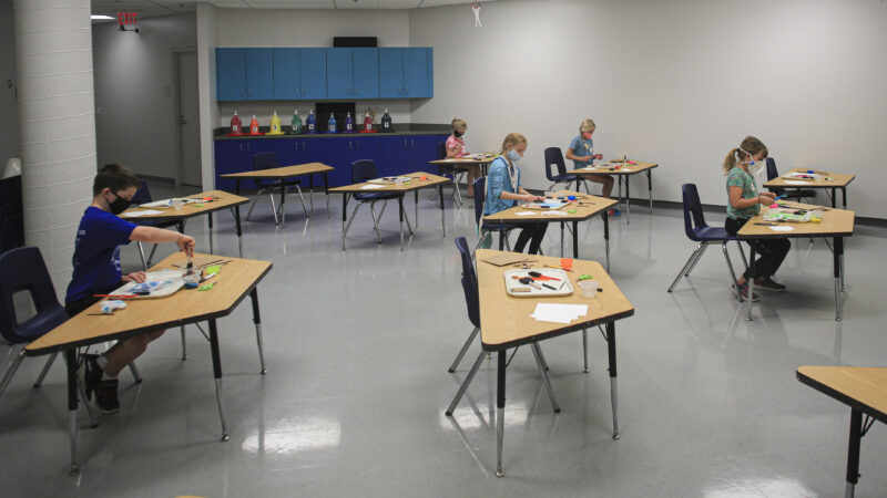 Young children working on art projects at tables spaced apart around a large room with white wallks and gray tile floor
