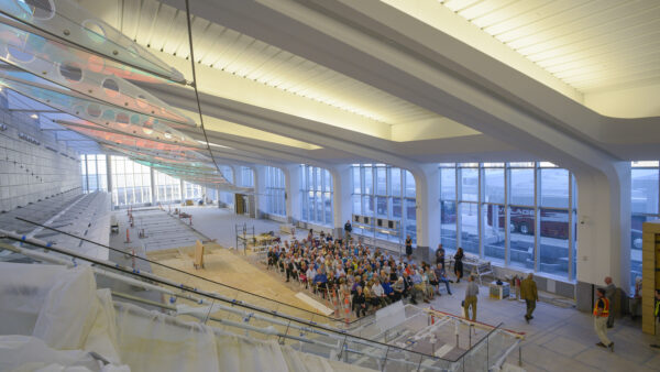 Large group of people in atrium underneath a large-scale wing-shaped sculpture at Eisenhower Airport unde