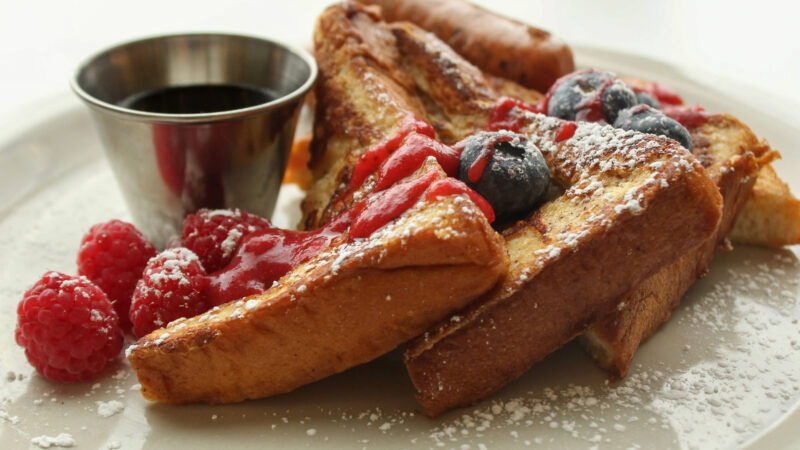 Three triangular pieces of french toast on a white plate covered with blueberries, raspberries, powdered sugar and garnished with a silver cup of syrup