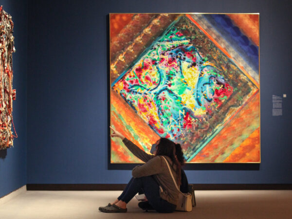 Photo of two people sitting on the floor in front of a colorful abstract painting, with one pointing to another painting on the all in front of them.
