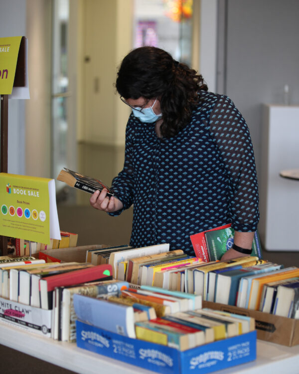 Woman in a face mask, looking at the back of a paperback book, standing in front of a table of books