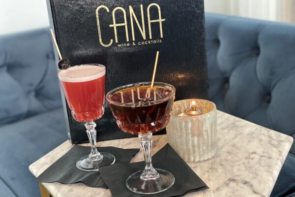 Cana Wine and Cocktails Menu behind two mixed drinks on a whiite lace tablecloth