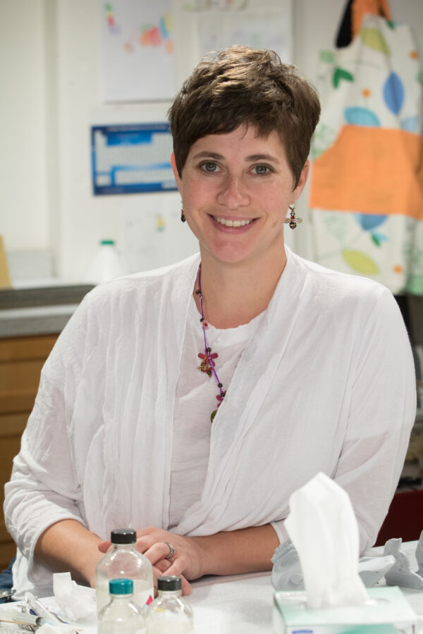 Woman with short hair and a white shirt with red earrings and red necklace looks directly at the camera with clear bottles and a box of facial tissues in front of her and a wall of printouts behind her