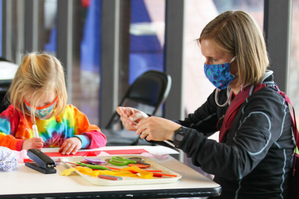Child in tie-die shirt and adult at a table making an art project
