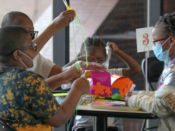 Four children around a table with artmaking supplies