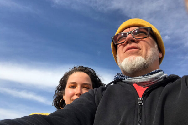 Photograph of a bearded man with glasses and weaing a knitted yellow cap with a woman with dark hair and weaing large gold hoop earrings looking over his shoulder