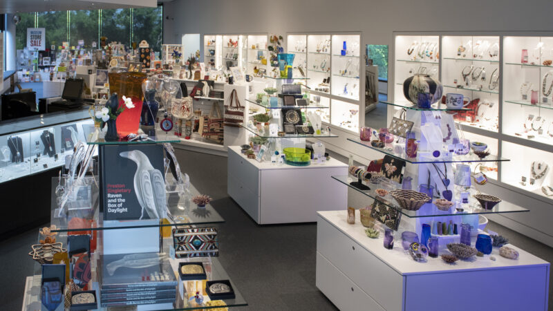 Interior view of the Museum Store showing three shelves displaying books and notecards with additional shelves of merchandise in the background