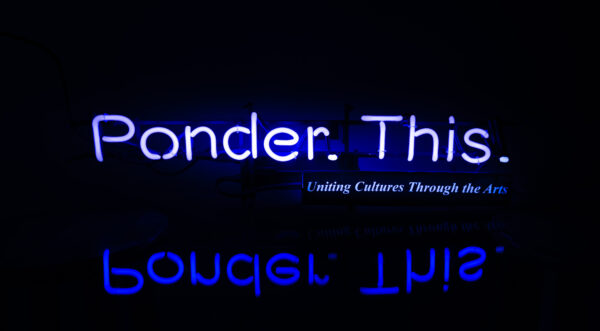 Neon blue text Ponder. This on a black baclground with a mirrored image below the text